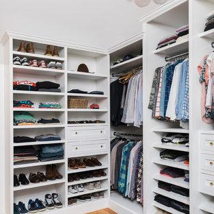 Modelo de armario vestidor unisex, bohemio, grande, con armarios estilo shaker, puertas de armario blancas y suelo de madera en tonos medios