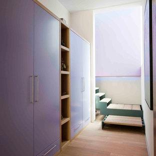 Foto di una grande cabina armadio unisex design con ante lisce, parquet chiaro e ante blu