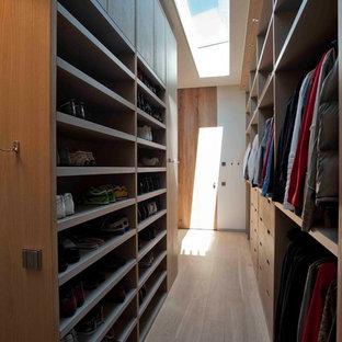 Diseño de armario vestidor unisex, contemporáneo, grande, con armarios con paneles lisos, puertas de armario de madera oscura y suelo de madera clara