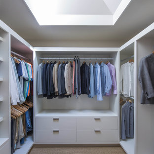 Foto di una cabina armadio minimal con ante bianche e nessun'anta