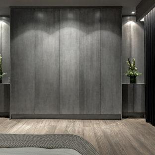 Ejemplo de armario y vestidor actual, grande, con armarios con paneles lisos, puertas de armario de madera en tonos medios y suelo de madera clara