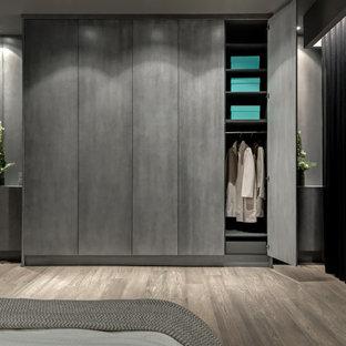 Foto di un grande armadio incassato design con ante lisce, ante in legno bruno e parquet chiaro