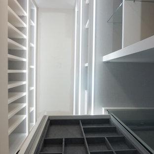 Modelo de armario vestidor unisex, minimalista, de tamaño medio, con armarios con paneles lisos, puertas de armario blancas y suelo de madera clara