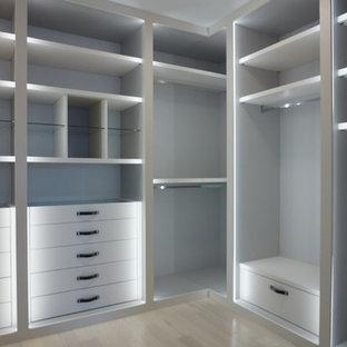 Пример оригинального дизайна интерьера: гардеробная комната среднего размера, унисекс в стиле модернизм с плоскими фасадами, белыми фасадами и светлым паркетным полом