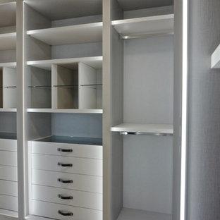 Ejemplo de armario vestidor unisex, minimalista, de tamaño medio, con armarios con paneles lisos, puertas de armario blancas y suelo de madera clara