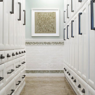 Large traditional gender-neutral dressing room in Other with limestone floors, recessed-panel cabinets, white cabinets and beige floor.