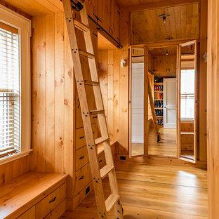 Ispirazione per una grande cabina armadio unisex tradizionale con ante in legno scuro e pavimento in legno massello medio