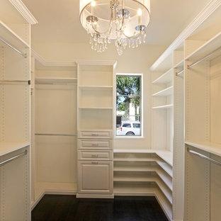 Foto de armario vestidor de mujer, mediterráneo, de tamaño medio, con armarios abiertos, puertas de armario blancas y suelo de madera oscura