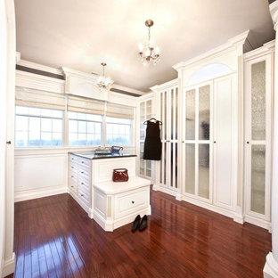 Modelo de armario vestidor tradicional, grande, con armarios tipo vitrina, puertas de armario blancas y suelo de madera en tonos medios