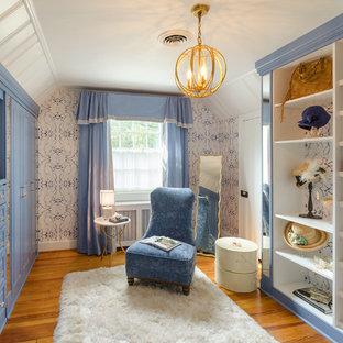 Foto de armario vestidor de mujer, clásico, con armarios con paneles con relieve, puertas de armario azules, suelo de madera en tonos medios y suelo marrón