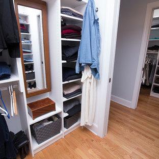 Diseño de armario vestidor unisex, clásico renovado, de tamaño medio, con armarios estilo shaker, puertas de armario blancas, suelo de madera en tonos medios y suelo naranja