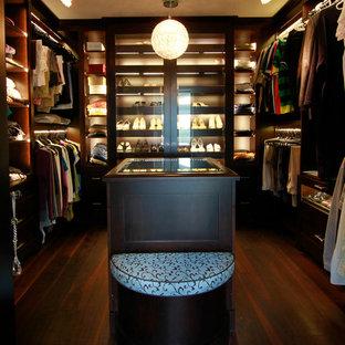 Imagen de armario vestidor unisex, tradicional renovado, de tamaño medio, con armarios abiertos, puertas de armario de madera en tonos medios y suelo de madera oscura