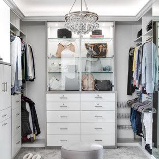 Ejemplo de armario vestidor de mujer, mediterráneo, de tamaño medio, con armarios con paneles lisos, puertas de armario blancas, moqueta y suelo gris