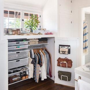 Modelo de vestidor unisex, de estilo americano, pequeño, con armarios con paneles con relieve, puertas de armario blancas y suelo de madera en tonos medios