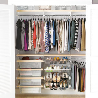 Photo of a large modern gender neutral standard wardrobe in Other with light hardwood flooring.