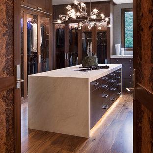 Bild på ett rustikt omklädningsrum för könsneutrala, med luckor med glaspanel, skåp i mörkt trä, mellanmörkt trägolv och brunt golv