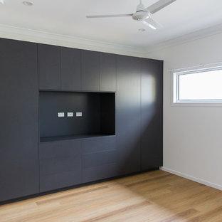 Foto de armario unisex, contemporáneo, de tamaño medio, con armarios con paneles lisos, puertas de armario grises, suelo vinílico y suelo marrón