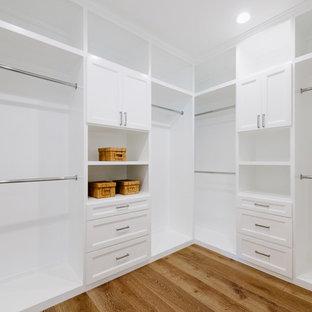 Ejemplo de armario vestidor unisex, clásico renovado, grande, con armarios con rebordes decorativos, puertas de armario blancas y suelo de madera clara