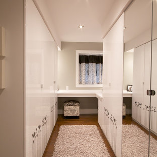 Dressing room - mid-sized contemporary women's dark wood floor and brown floor dressing room idea in Montreal with flat-panel cabinets and white cabinets