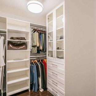 Ejemplo de armario vestidor unisex, tradicional, pequeño, con armarios tipo vitrina, puertas de armario blancas, suelo de madera oscura y suelo marrón