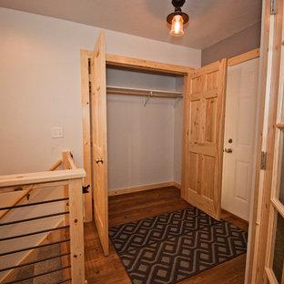Ejemplo de armario unisex, rural, de tamaño medio, con suelo de madera en tonos medios y suelo marrón