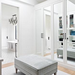 トロントの女性用トランジショナルスタイルのおしゃれなフィッティングルーム (落し込みパネル扉のキャビネット、白いキャビネット、淡色無垢フローリング、三角天井) の写真