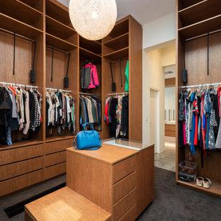 Ejemplo de vestidor unisex, contemporáneo, grande, con puertas de armario de madera oscura, moqueta y suelo gris