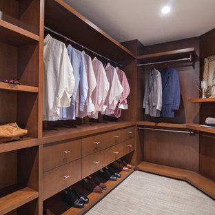 Idée de décoration pour un dressing minimaliste de taille moyenne pour un homme avec un placard à porte plane, des portes de placard en bois sombre, moquette et un sol beige.