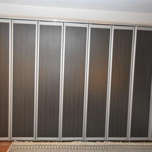 Imagen de armario de hombre, contemporáneo, pequeño, con armarios con paneles con relieve, puertas de armario marrones y suelo de madera en tonos medios