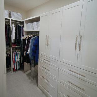 Immagine di una piccola cabina armadio unisex minimalista con ante con riquadro incassato, ante bianche, moquette e pavimento beige
