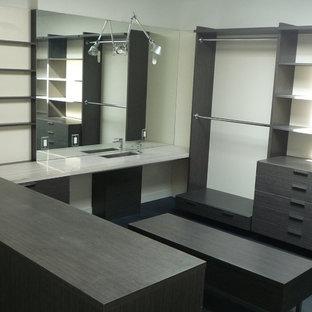 Diseño de armario vestidor unisex, minimalista, grande, con armarios con paneles lisos, puertas de armario grises, suelo de madera pintada y suelo negro
