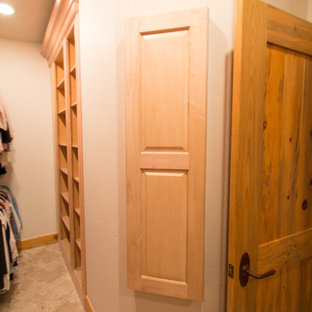 This is an example of a large classic gender neutral walk-in wardrobe in Denver with raised-panel cabinets, light wood cabinets, travertine flooring and beige floors.