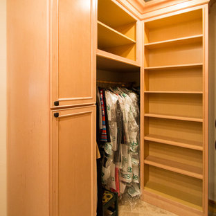 Inspiration for a large traditional gender neutral walk-in wardrobe in Denver with raised-panel cabinets, light wood cabinets, travertine flooring and beige floors.