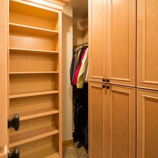 Diseño de armario vestidor unisex, tradicional, grande, con armarios con paneles con relieve, puertas de armario de madera clara, suelo de travertino y suelo beige