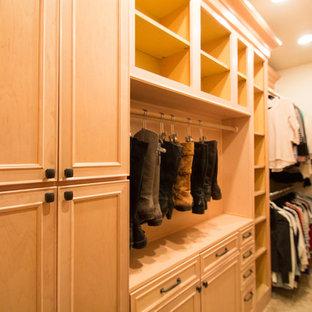 Modelo de armario vestidor unisex, clásico, grande, con armarios con paneles con relieve, puertas de armario de madera clara, suelo de travertino y suelo beige
