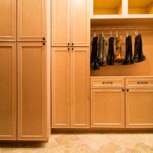Imagen de armario vestidor unisex, clásico, grande, con armarios con paneles con relieve, puertas de armario de madera clara, suelo de travertino y suelo beige