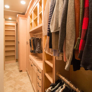 Large classic gender neutral walk-in wardrobe in Denver with raised-panel cabinets, light wood cabinets, travertine flooring and beige floors.