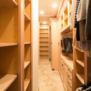 Imagen de armario vestidor unisex, tradicional, grande, con armarios con paneles con relieve, puertas de armario de madera clara, suelo de travertino y suelo beige