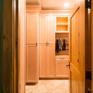This is an example of a large traditional gender neutral walk-in wardrobe in Denver with raised-panel cabinets, light wood cabinets, travertine flooring and beige floors.