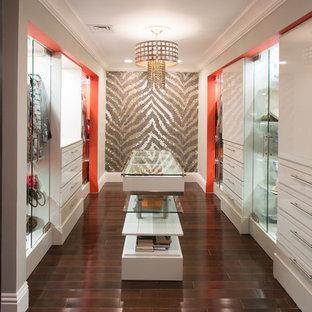 Ispirazione per una cabina armadio unisex design di medie dimensioni con ante lisce, ante bianche, parquet scuro e pavimento marrone