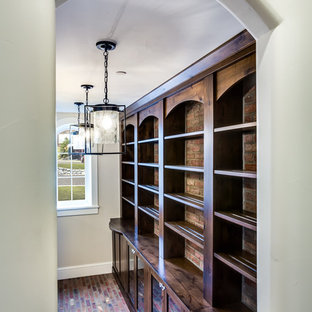 Idée de décoration pour un grand dressing tradition neutre avec un placard à porte shaker, des portes de placard en bois brun et un sol en brique.