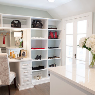 This is an example of a large country gender-neutral dressing room in Chicago with white cabinets, medium hardwood floors and raised-panel cabinets.
