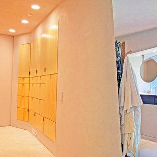 Ispirazione per uno spazio per vestirsi unisex minimalista di medie dimensioni con ante lisce, ante in legno chiaro e pavimento in cemento