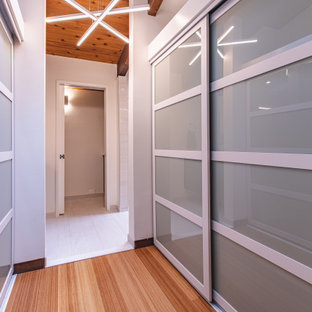 Aménagement d'un dressing room rétro de taille moyenne avec un placard à porte plane, des portes de placard marrons, un sol en bambou, un sol marron et un plafond voûté.