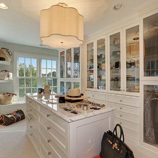 Ispirazione per un'ampia cabina armadio per donna chic con ante bianche, moquette, ante di vetro e pavimento beige