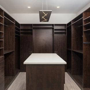 Ejemplo de armario vestidor unisex, actual, grande, con armarios con paneles lisos, puertas de armario de madera en tonos medios, suelo de baldosas de porcelana y suelo marrón