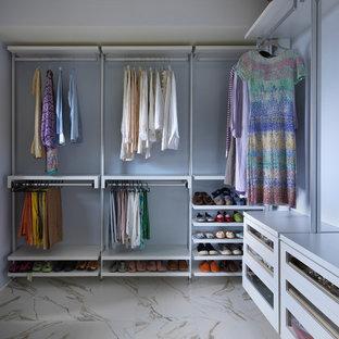 Diseño de armario vestidor unisex, actual, de tamaño medio, con armarios con paneles lisos, puertas de armario blancas y suelo de mármol