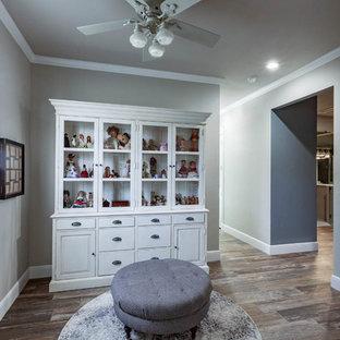Ejemplo de vestidor de mujer, de estilo de casa de campo, con armarios tipo vitrina, puertas de armario con efecto envejecido, suelo de baldosas de porcelana y suelo marrón