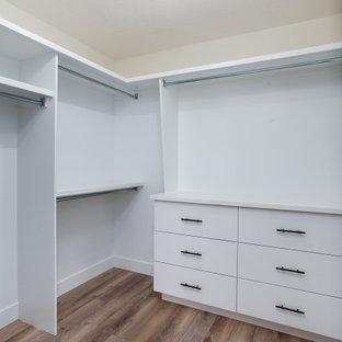 Ejemplo de armario vestidor unisex, campestre, grande, con armarios con paneles lisos, puertas de armario blancas, suelo vinílico y suelo marrón