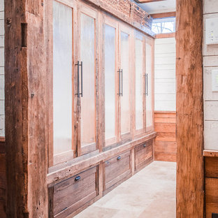 Design ideas for a country gender-neutral walk-in wardrobe in New York with glass-front cabinets and distressed cabinets.